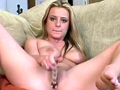 Busty blonde masturbating with dildo on couch