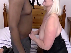 Busty granny blowing black dick